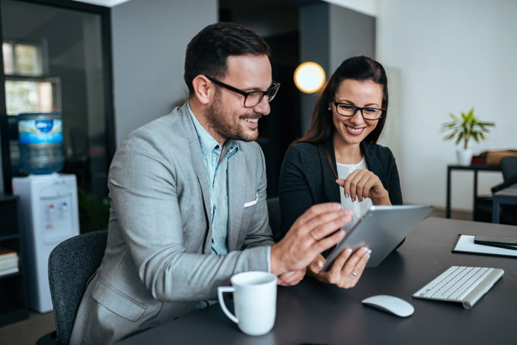 Geschäftsmann Geschäftsfrau schauen lächelnd auf Tablet im Büro