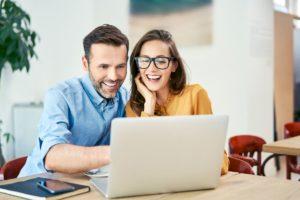 Mann und Frau sitzen lächelnd vor Laptop