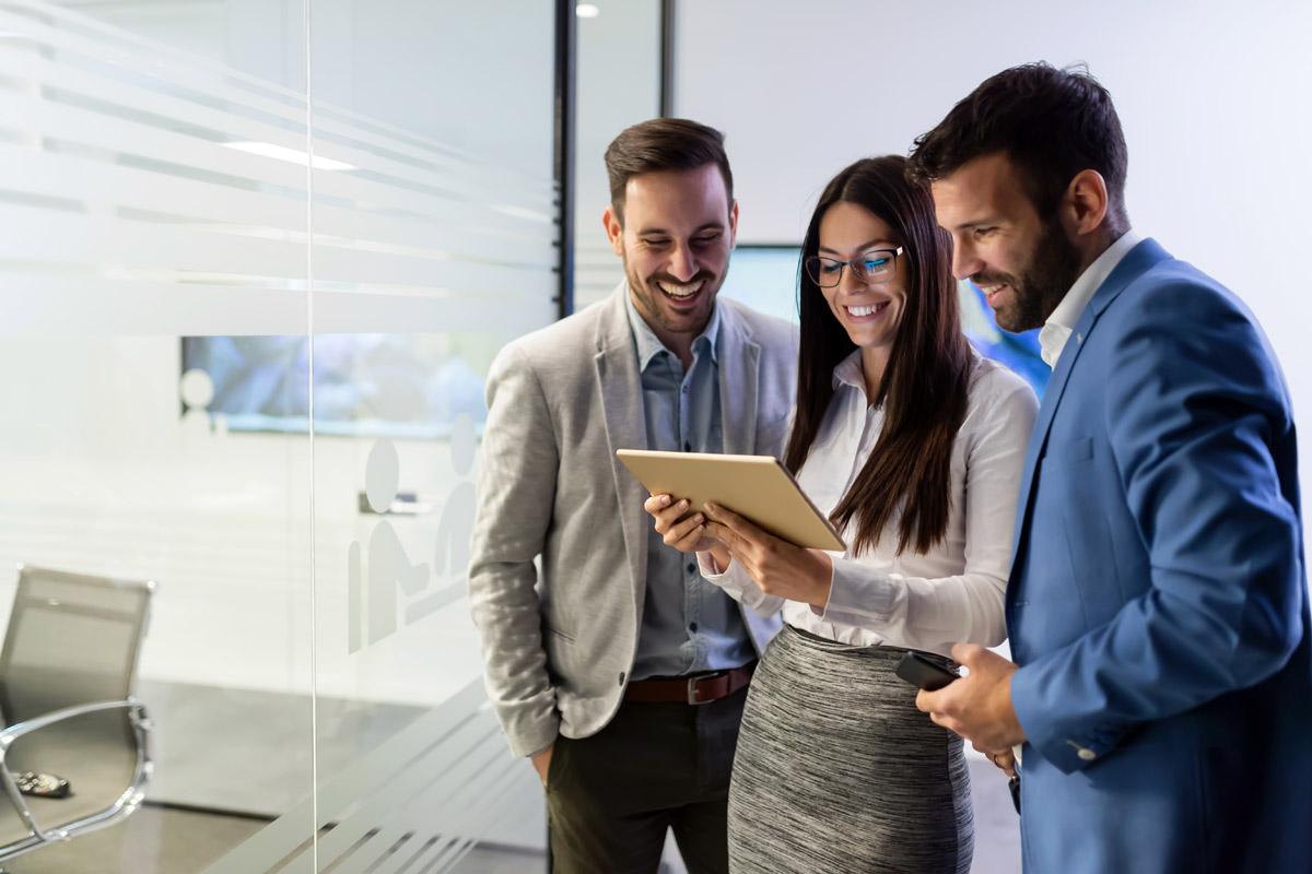 Geschäftsleute schauen lächelnd auf Tablet