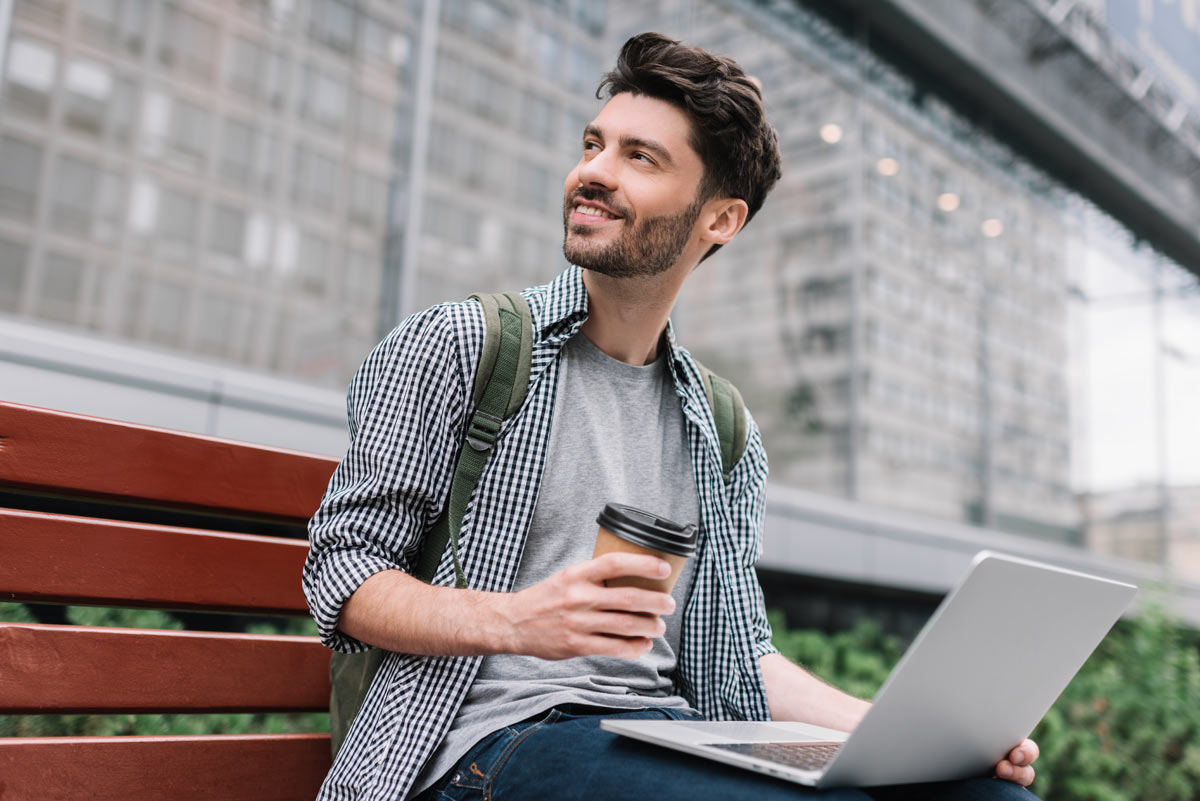 Mann mit Laptop und Kaffee in der Hand