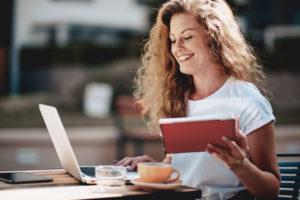Junge Frau Kaffee lacht lernt Laptop Notizen