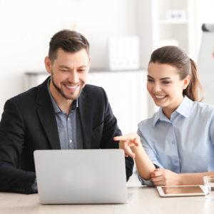 Mann und Frau sitzen vor Laptop und lächeln