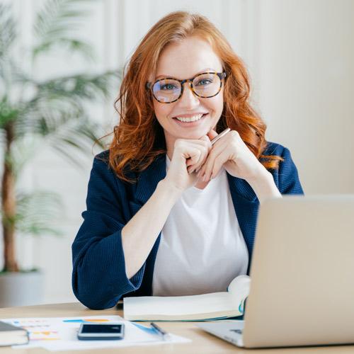 Rothaarige Frau sitzt vor Laptop