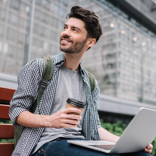 Mann hält Laptop und PC in der Hand