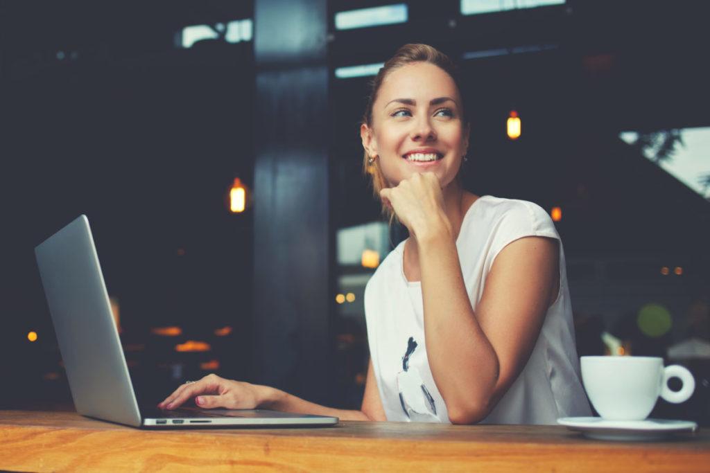 Frau sitzt lächelnd vor Laptop