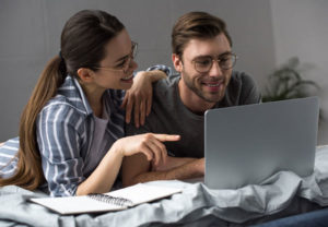 Paar fröhlich Bett Laptop Webinar