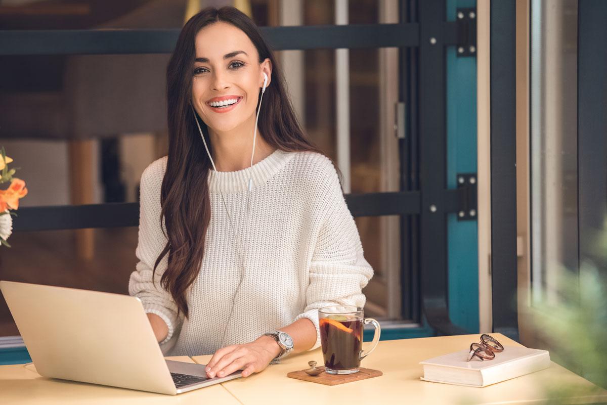 Frau lacht Kopfhörer Laptop Arbeitsplatz