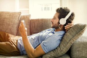 Mann liegt auf Sofa mit Kopfhörern und Handy
