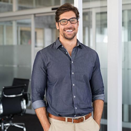 Mann mit dunklem Hemd und Brille lächelt