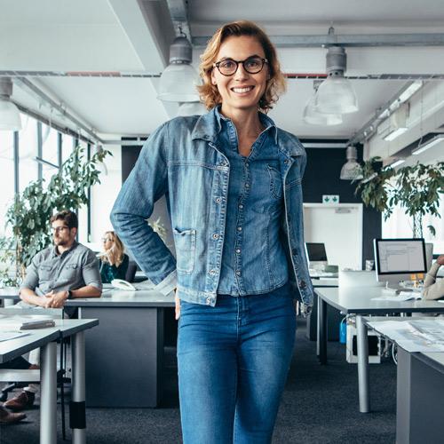 Frau in Jeans steht im Büro und lächelt