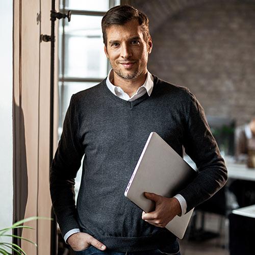 Mann mit Laptop im Arm