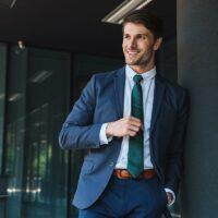 Attraktiver Geschäftsmann lehnt an Säule und lächelt