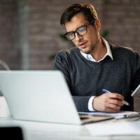 Businessman schreibt etwas von Laptop auf