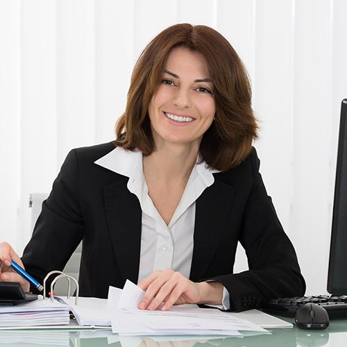 Frau sitzt an Schreibtisch und lächelt