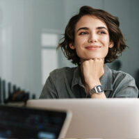 Junge Frau mit zufriedenem Blick vor Laptop.