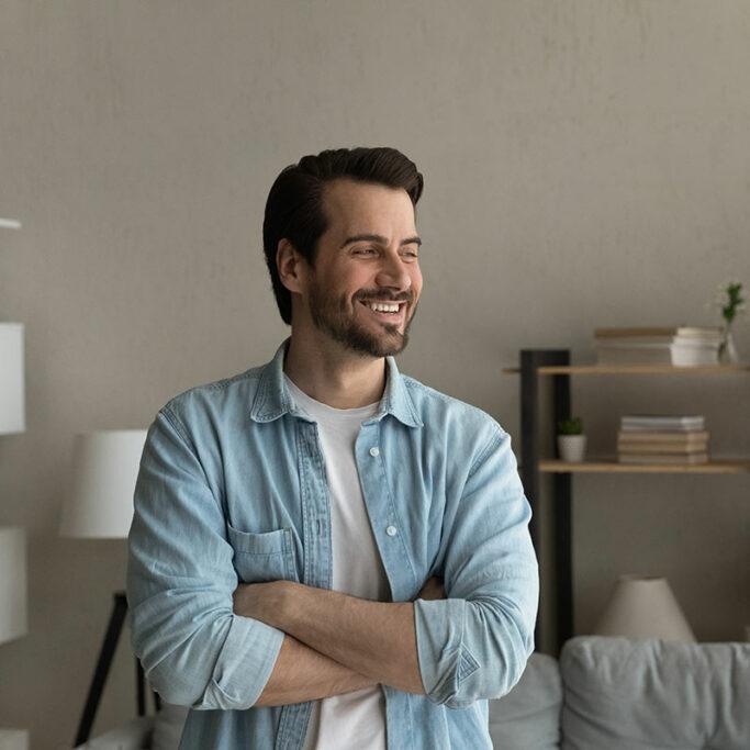 Junger Mann steht im Wohnzimmer