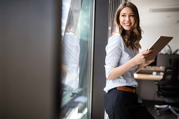 Frau an Fensterscheibe gelehnt lächelt