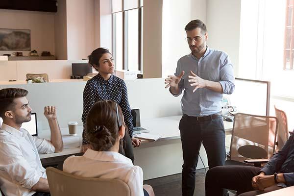 Mann steht vor Gruppe und erklärt