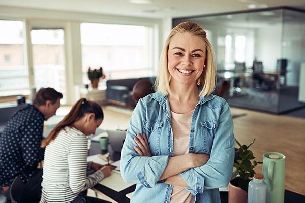 Frau mit verschränkten Armen lächelt