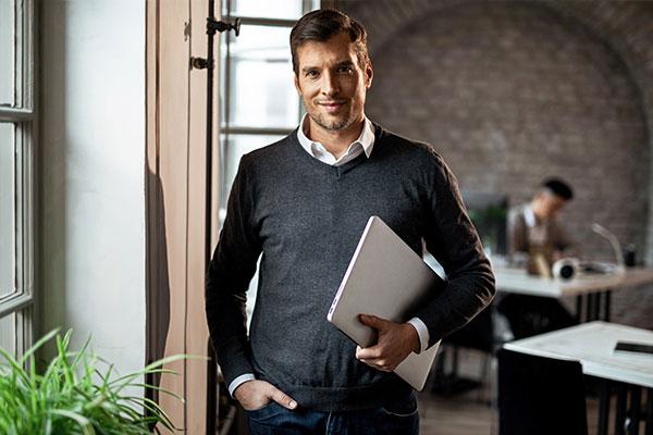 Mann mit Laptop unter dem Arm steht im Büro und lächelt in die Kamera