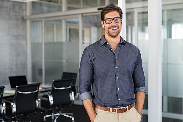 Lächelnder Mann steht im Büro