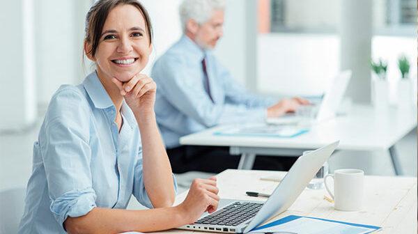 Frau sitzt vor Laptop im Büro