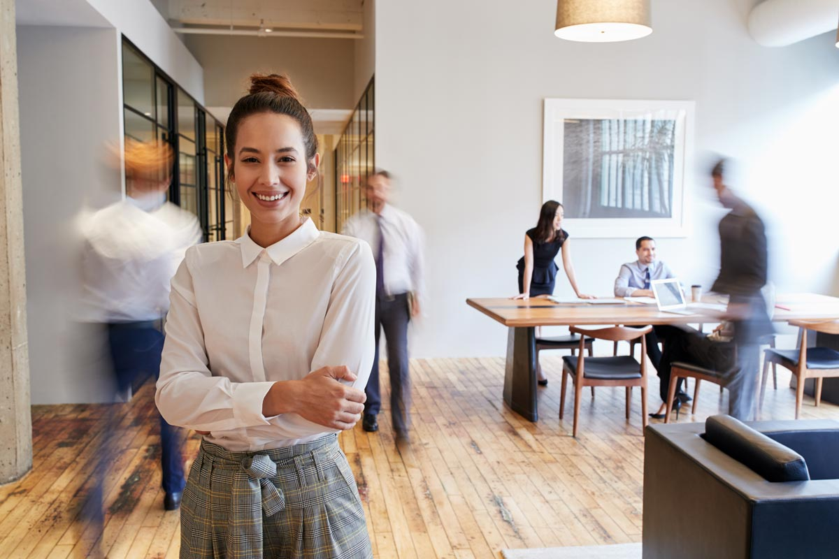 Lächelnde Frau steht im Büro
