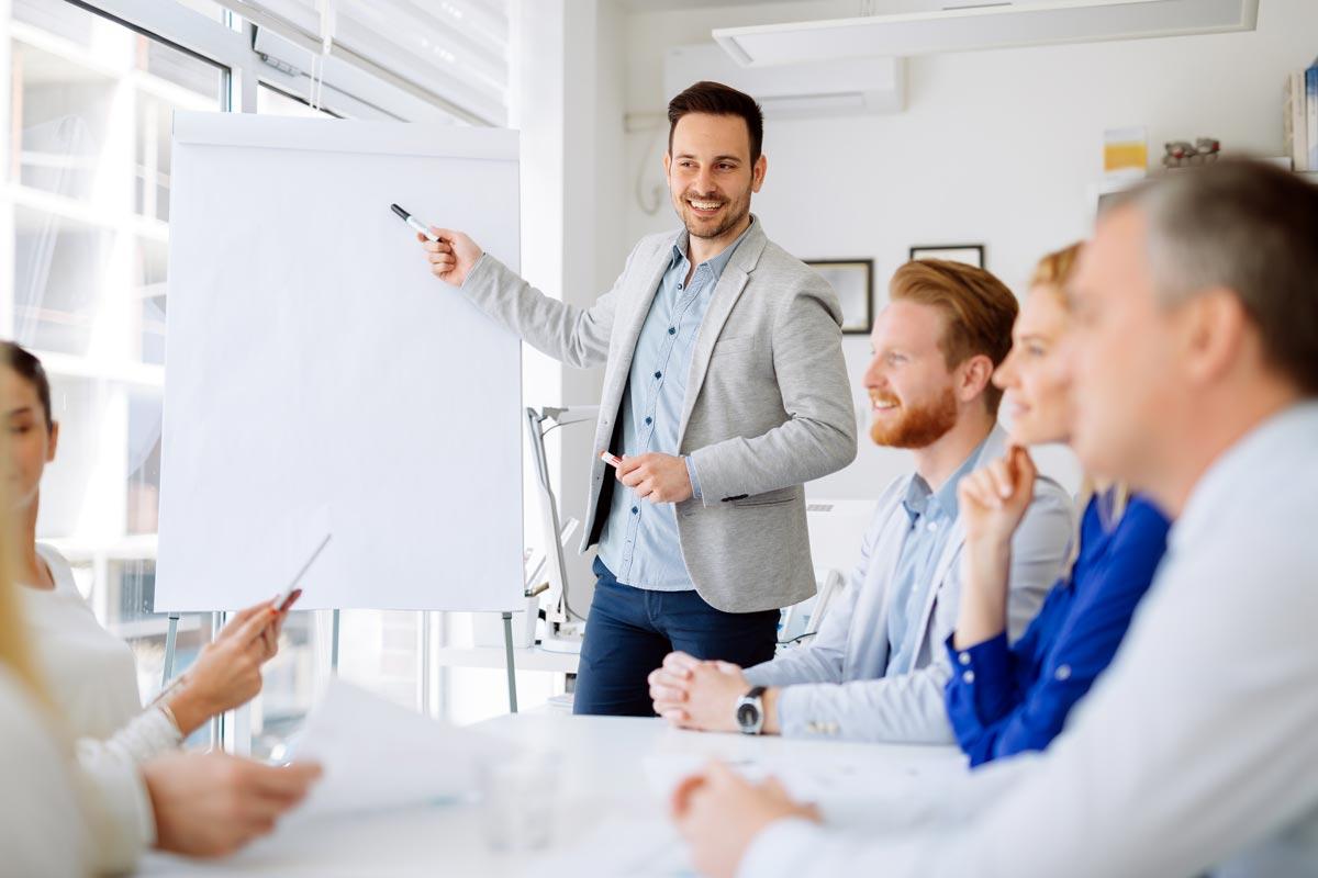 Business Meeting. Mann im Mittelpunkt erklärt etwas.