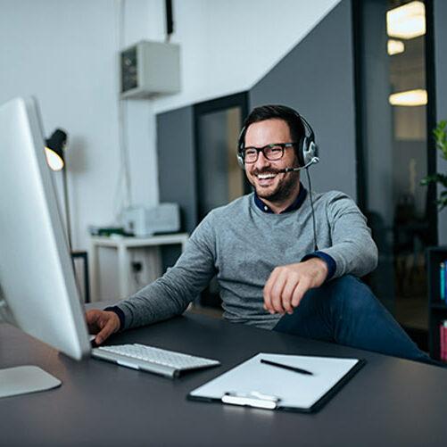 Mann sitzt im Büro und hat ein Meeting am PC