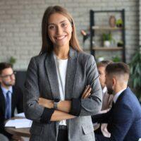 Frau steht im Vordergrund und lächelt in die Kamera. Meeting mit drei Personen im Hintergrund.