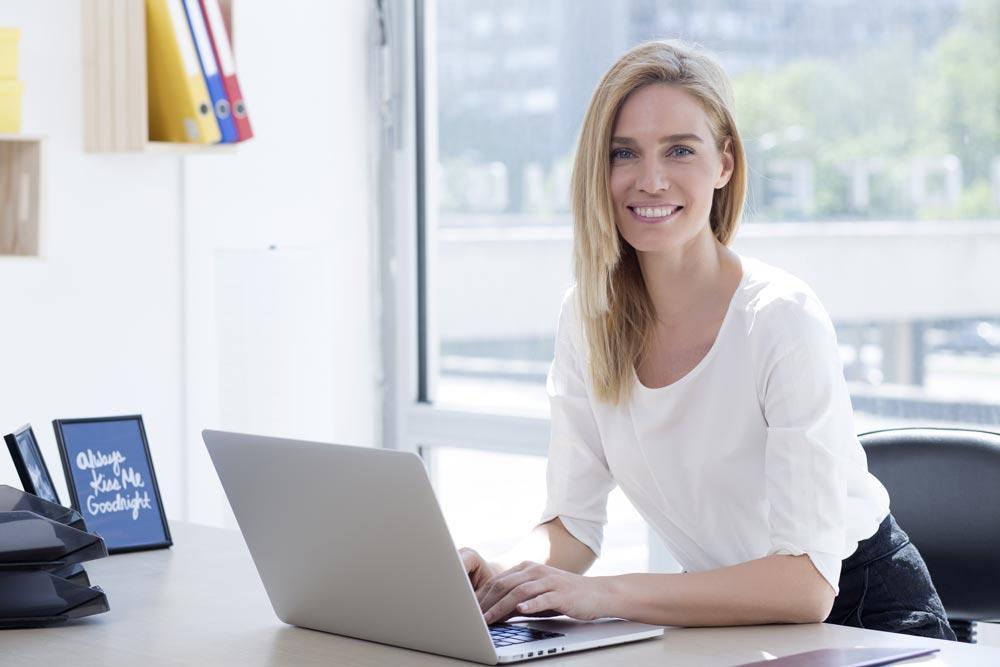 lachende Frau im Büro sitzt vor Laptop