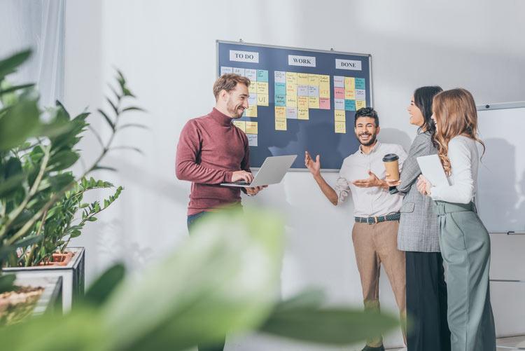 Business Meeting. Team steht vor Board mit To-Do Liste