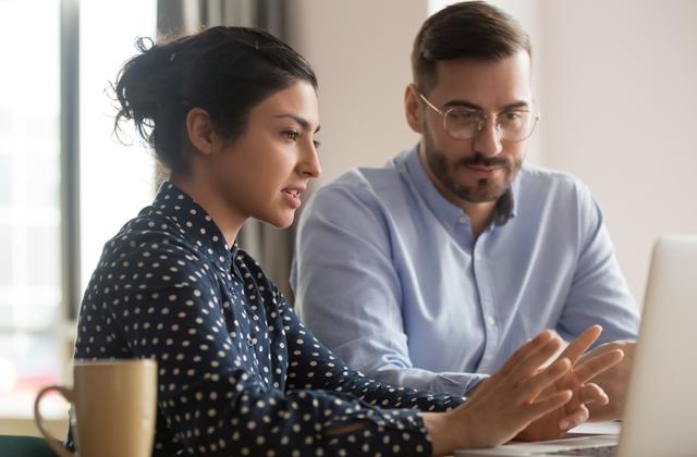 Frau erklärt Mann vor Laptop etwas