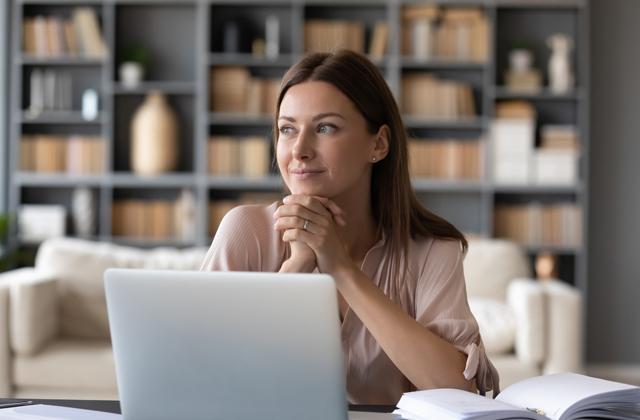 Frau sitzt vor Laptop und sieht zur Seite