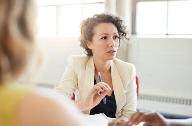Frau im Meeting mit zwei anderen Personen