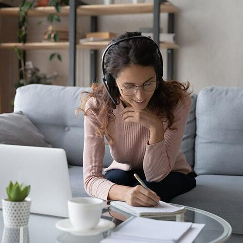 Junge Frau sitzt auf der Couch vor Laptop und schreibt etwas in einen Notizblock.