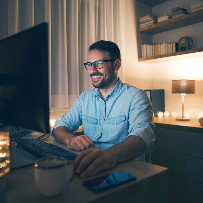 Mann mit Brille sitzt abends vor PC