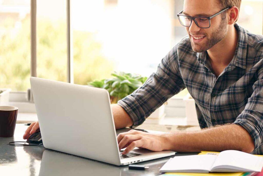 Junger Mann mit Brille schreibt etwas am Laptop