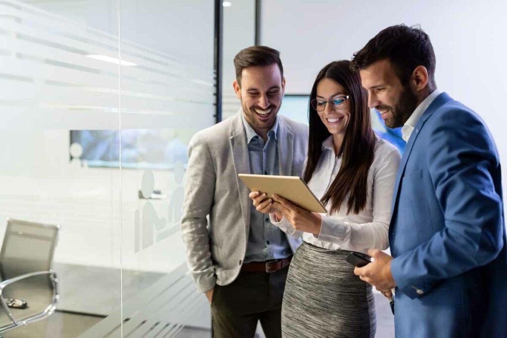 Junge Frau und zwei Männer im Meeting. Sie schauen auf ein Tablet.