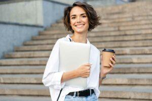 Junge Frau mit Laptop und Kaffee in der Hand steht auf einer Stiege