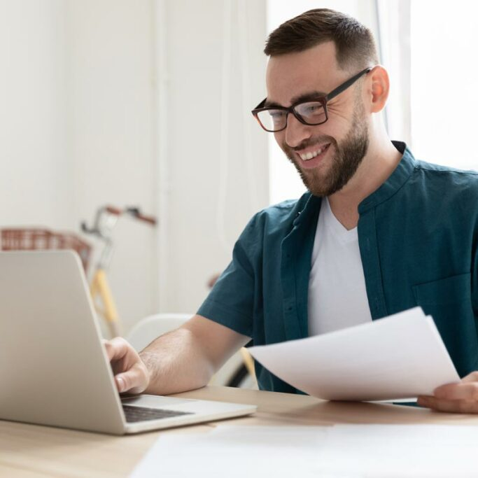 Mann mit Brille sitzt vor Laptop