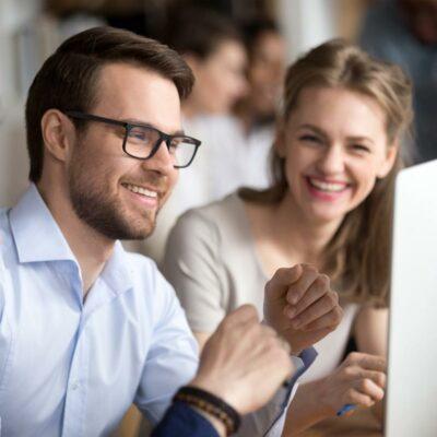 Mann und Frau lächelnd vor PC