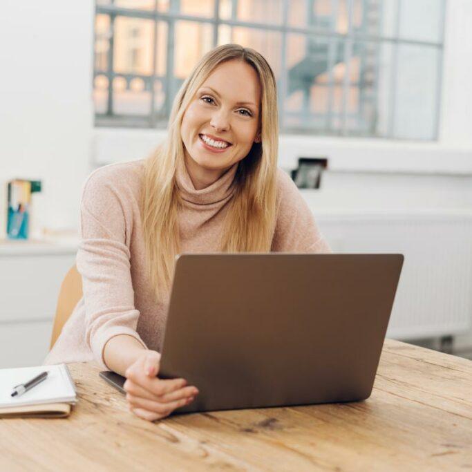 Junge Frau mit Laptop im Büro sieht lachend in die Kamera