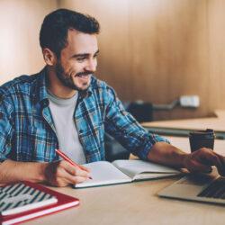 Junger Männlicher Student lernt etwas vor dem Laptop