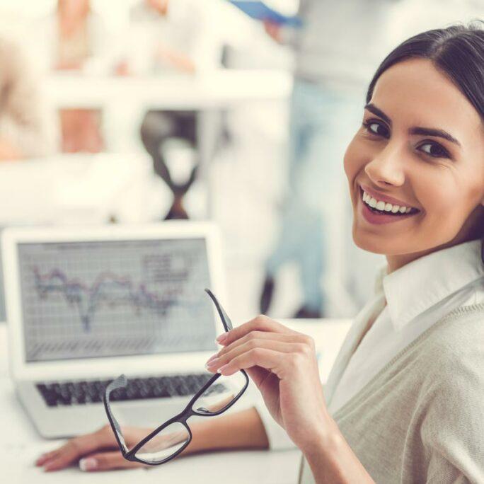 Junge Business Frau vor Laptop lächelnd