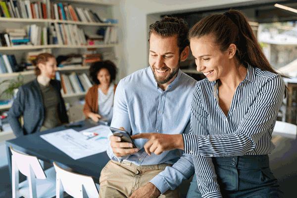 Mann und Frau starren lächelnd auf Handy
